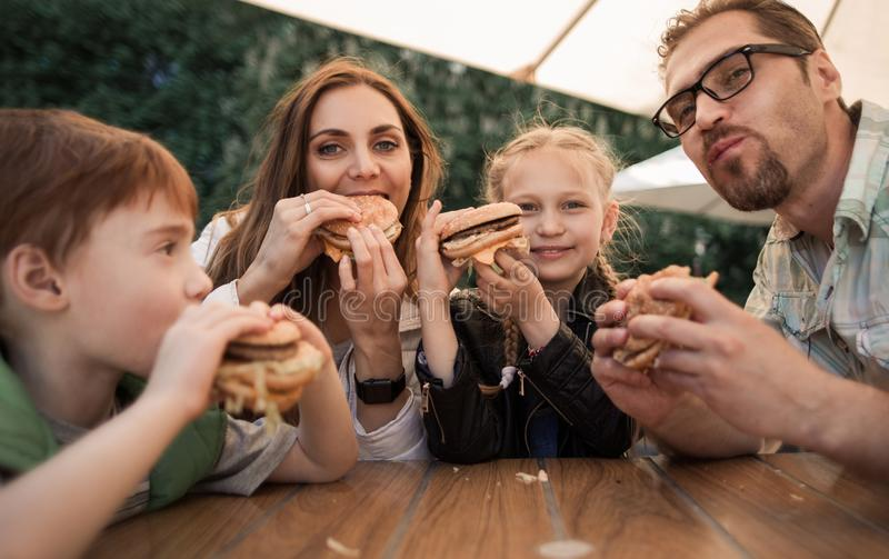 Happy family eating burgers sitting at a table in a cafe royalty free stock photos