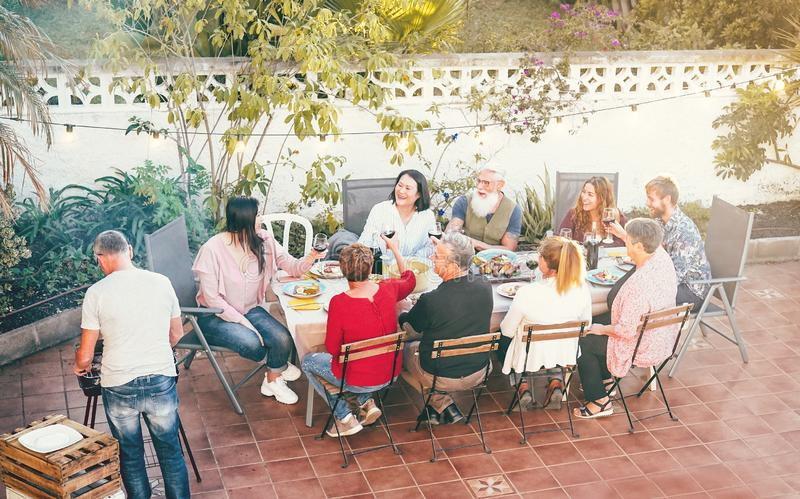 Happy family eating and drinking red wine at dinner barbecue outdoor - People with different ages having fun dining together royalty free stock photo