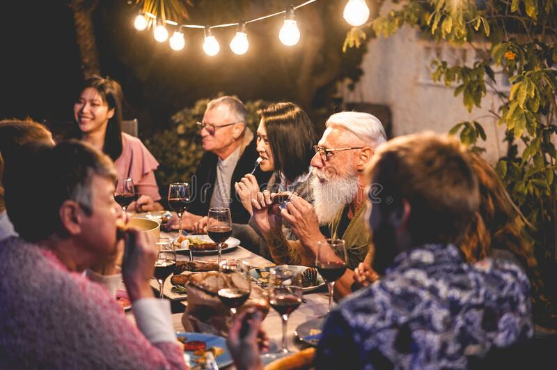 Happy family eating and drinking wine at barbecue dinner outdoor - Multiracial mature and young people having fun at bbq sunday. Meal - Food and summer stock images