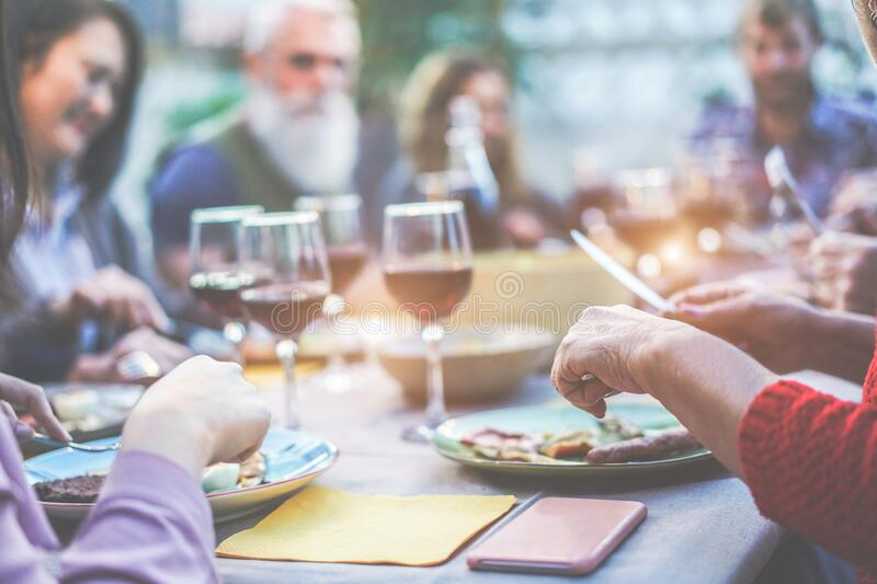 Happy family eating and drinking wine at barbecue dinner on patio outdoor - Mature and young people having fun at bbq sunday meal. Food and summer lifestyle royalty free stock images