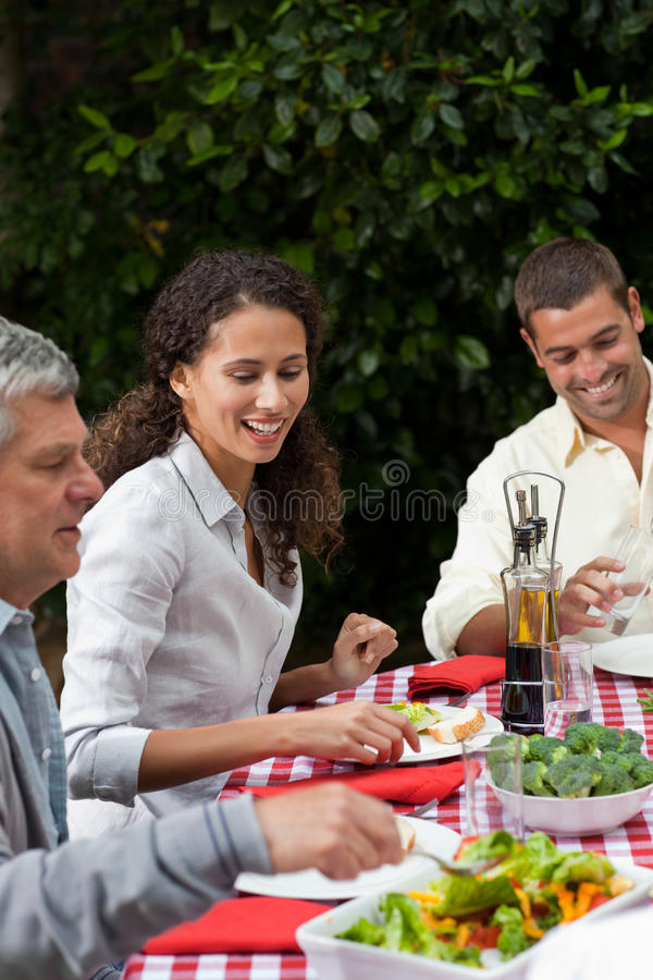 Happy family eating in the garden. Happy family eating together in the garden royalty free stock photo