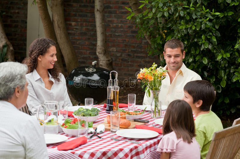Happy family eating in the garden. And having a good time stock photo
