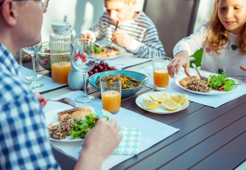 Happy family eating healthy dinner on terrace at home stock photography