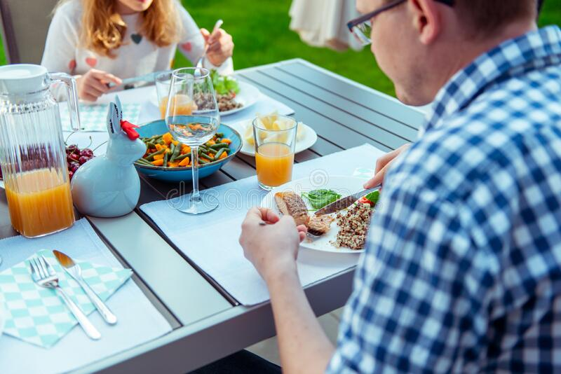 Happy family eating healthy dinner on terrace at home royalty free stock photo