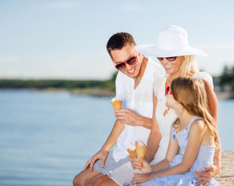 Happy family eating ice cream. Summer holidays, celebration, children and people concept - happy family eating ice cream stock images