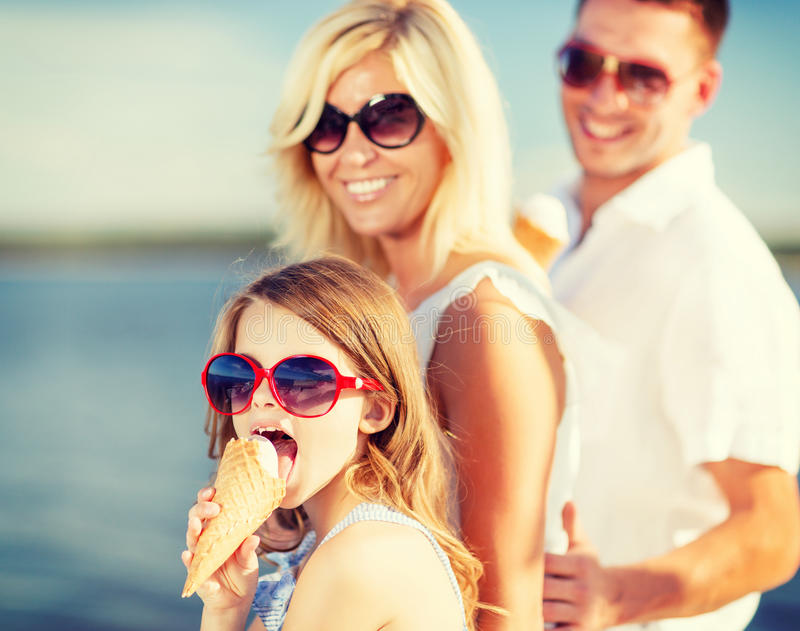 Happy family eating ice cream. Summer holidays, celebration, children and people concept - happy family eating ice cream royalty free stock images