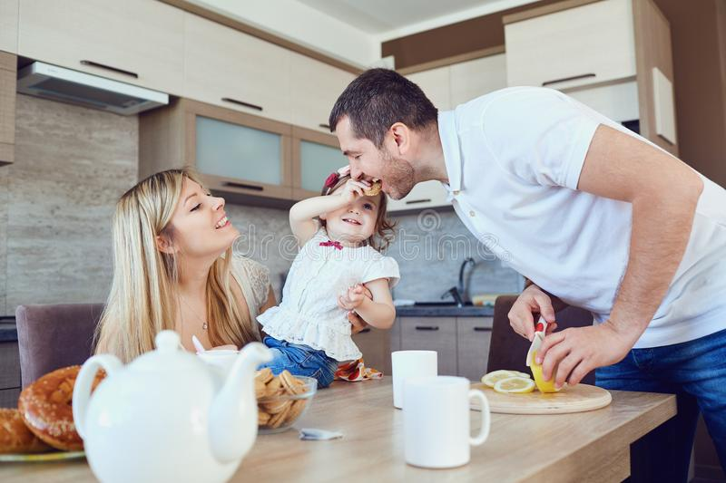A happy family is eating in the kitchen. A happy family is eating in the kitchen while sitting at a table stock image