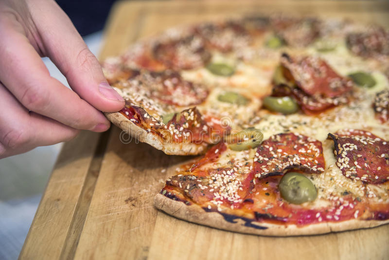 Happy family eating pizza on the wooden table. Hands taking pizza from table, closeup. food, leisure and friendship concept.  royalty free stock photo