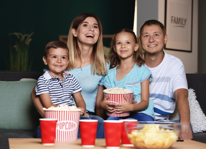 Happy family eating popcorn while watching TV in evening stock images