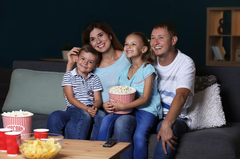 Happy family eating popcorn while watching TV in evening royalty free stock images