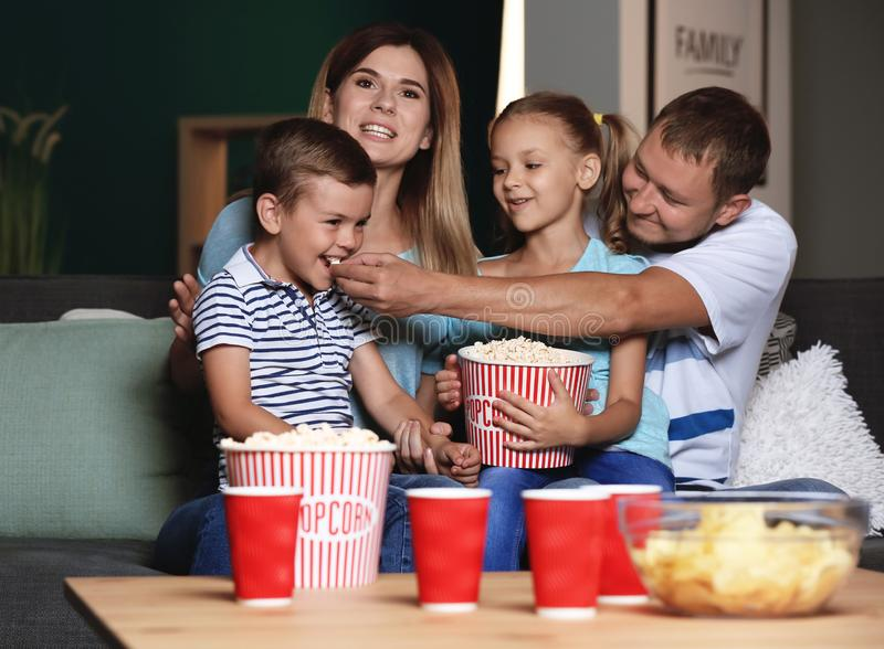 Happy family eating popcorn while watching TV in evening royalty free stock photos
