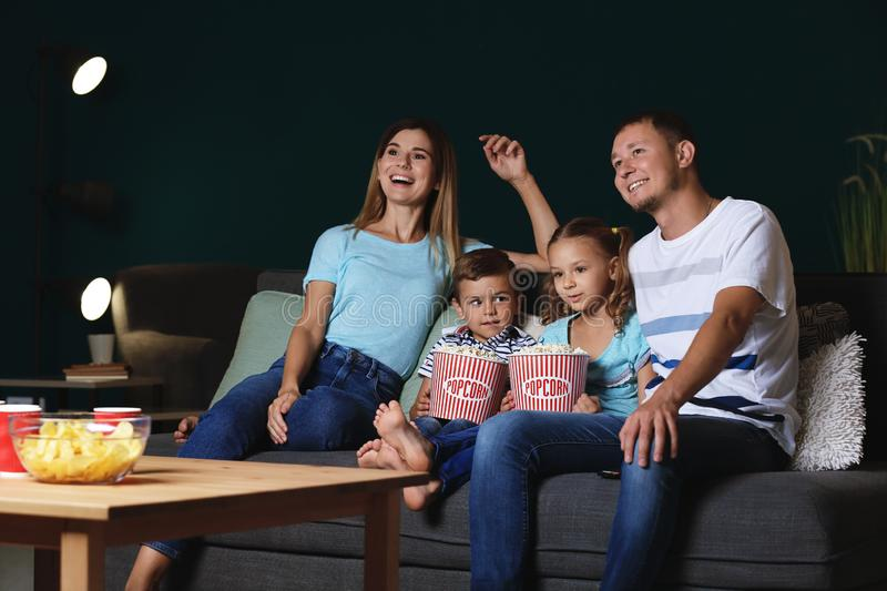 Happy family eating popcorn while watching TV in evening stock image