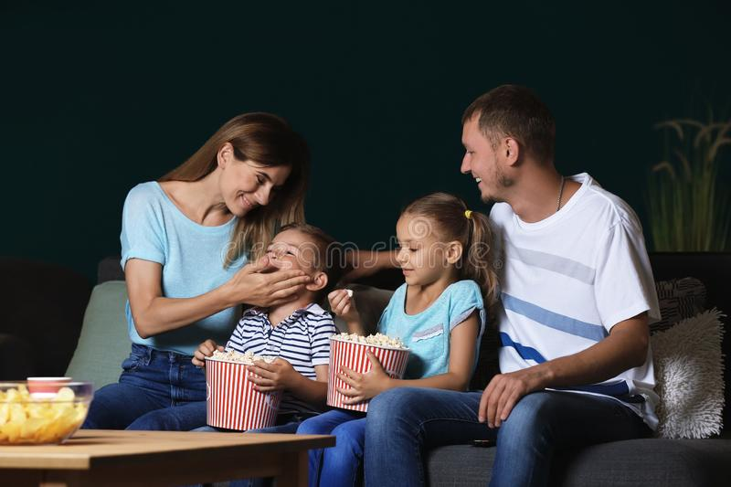 Happy family eating popcorn while watching TV in evening royalty free stock photography
