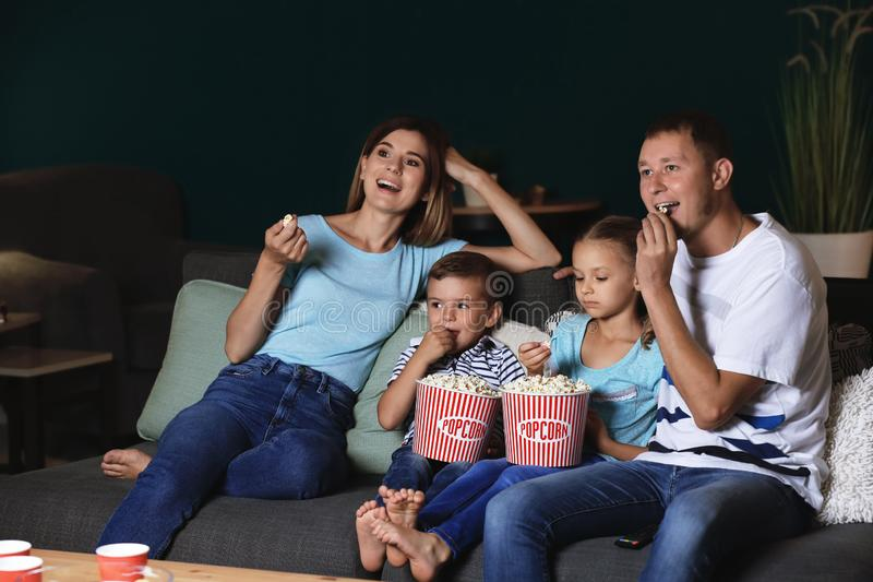 Happy family eating popcorn while watching TV in evening stock photography