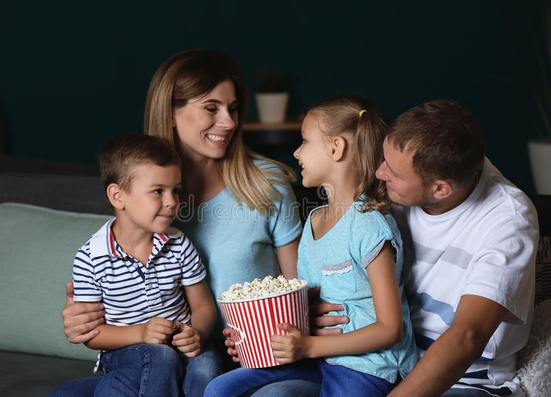 Happy family eating popcorn while watching TV in evening stock photo