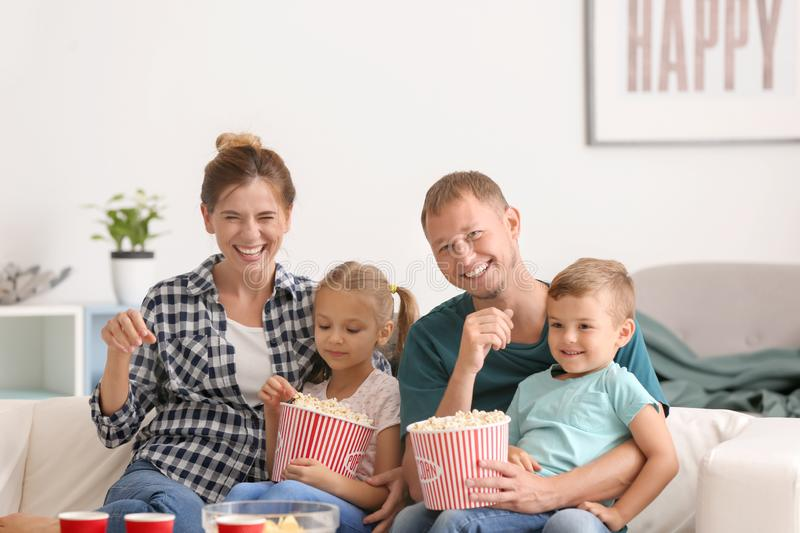 Happy family eating popcorn while watching TV at home stock images