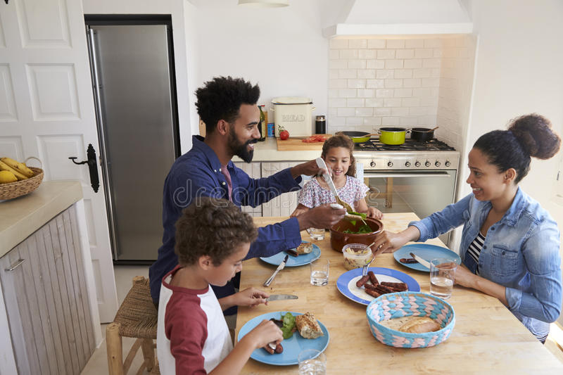 Happy family eating together at their kitchen table royalty free stock images