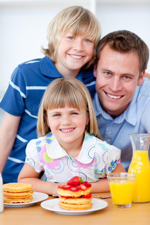 Happy family eating waffles with strawberries. In the kitchen royalty free stock images