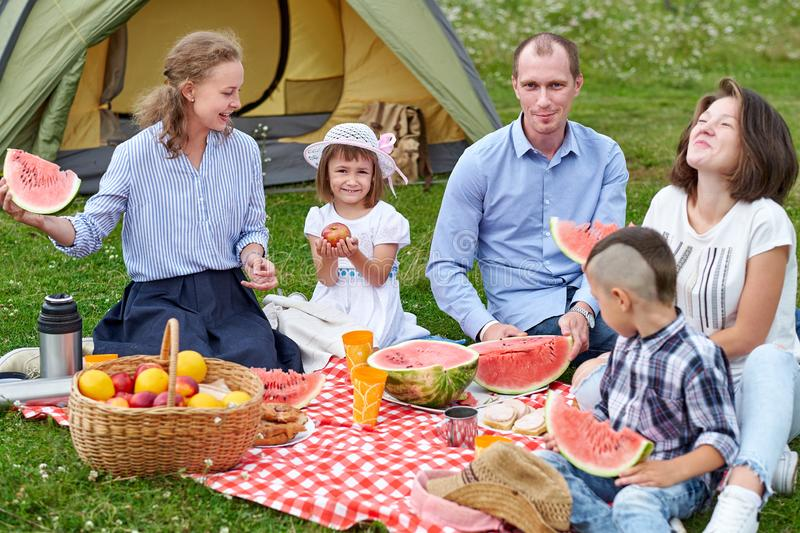 Happy family eating watermelon at picnic in meadow near the tent. Family Enjoying Camping Holiday In Countryside.  royalty free stock image