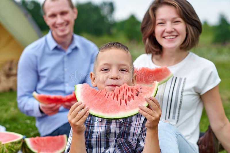 Happy family eating watermelon at picnic in meadow near the tent. Mother, father and child Enjoying Camping Holiday In Countryside.  stock photo
