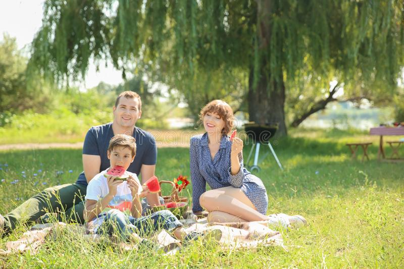 Happy family eating watermelon on summer picnic in park stock photos