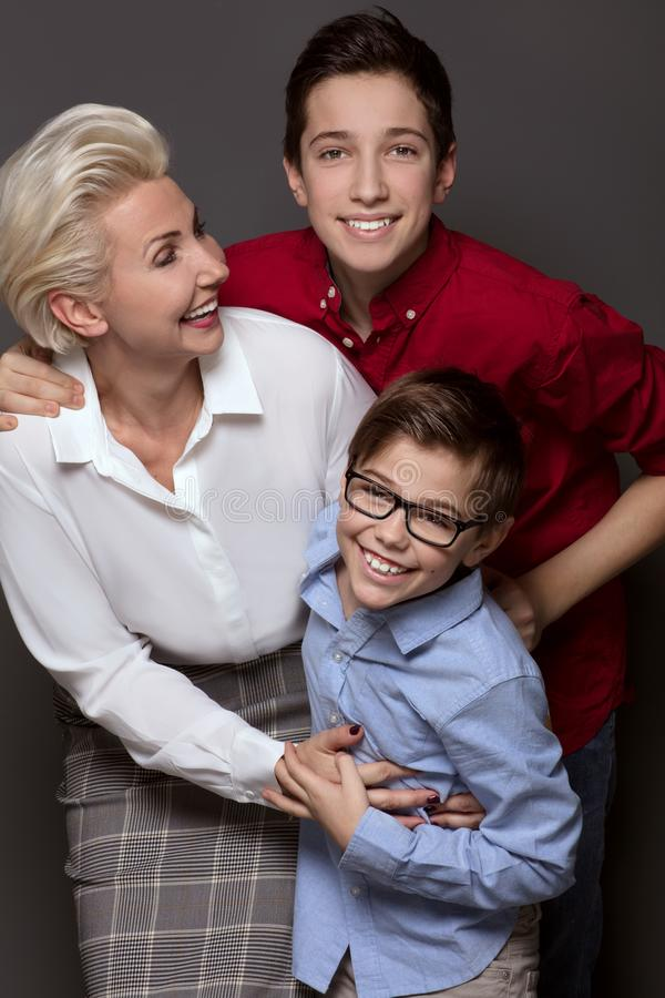 Happy mother posing with two sons. stock image
