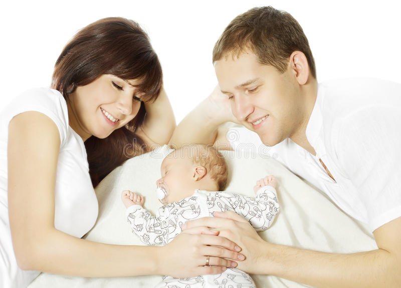 Happy family embracing sleeping newborn baby. Parents and child over white background stock photo