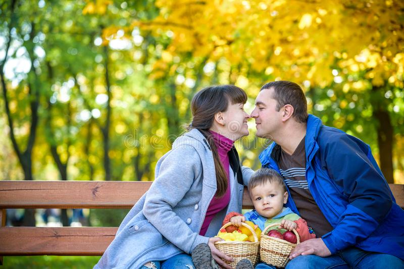 Happy family enjoying autumn picnic. Father mother and son sit on bench with apples basket. Happy family leisure together concept stock images