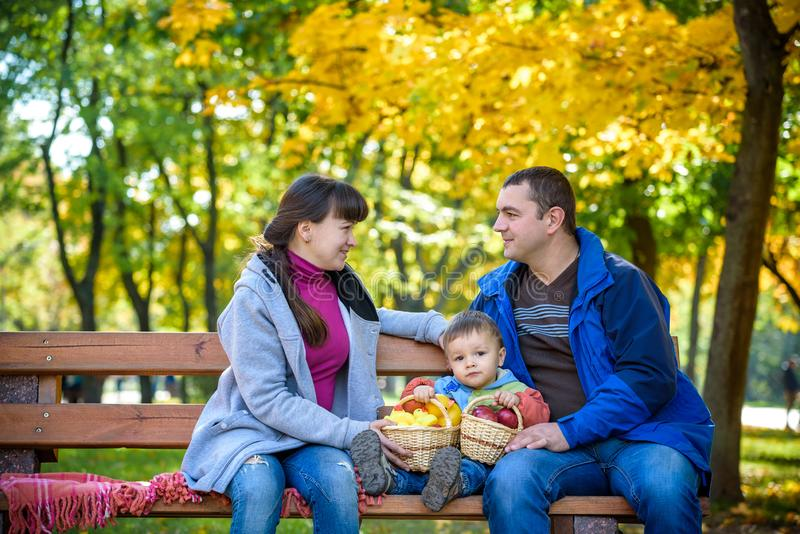 Happy family enjoying autumn picnic. Father mother and son sit o stock image