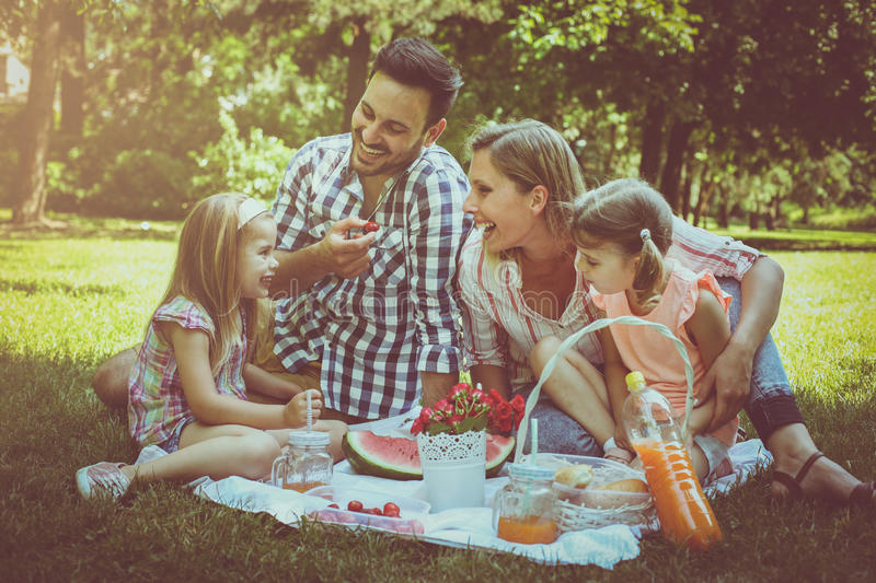 Happy family enjoying in picnic together. Family in meadow royalty free stock photo