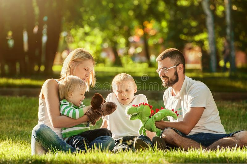 Happy family enjoying sunny day playing in the park stock images