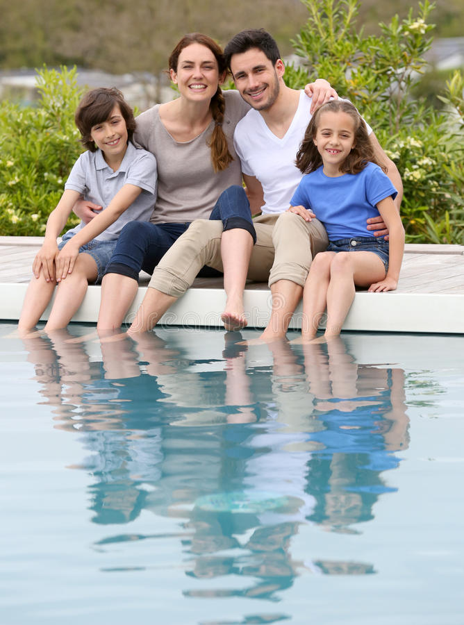 Happy family enjoying by swimming pool. Parents with children relaxing by the pool stock photography