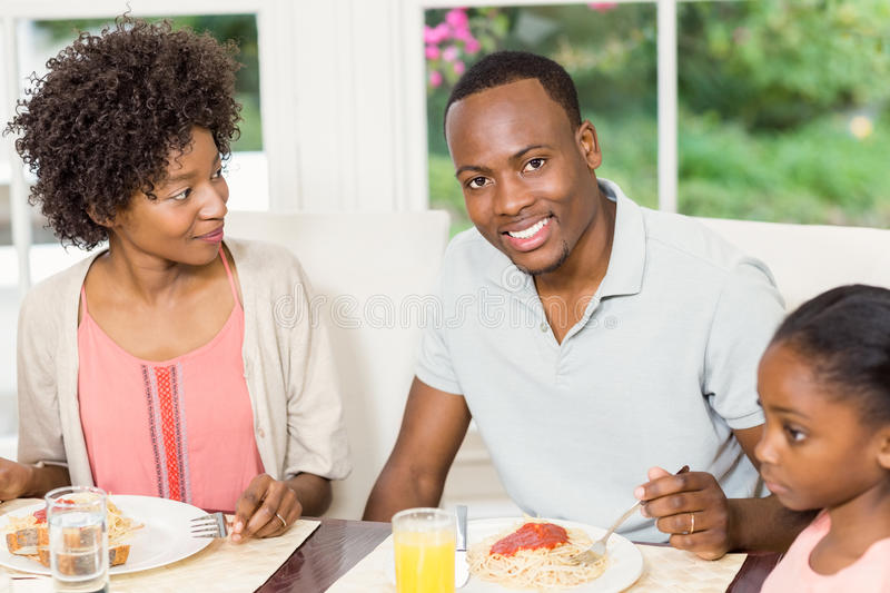 Happy family enjoying their meal stock image