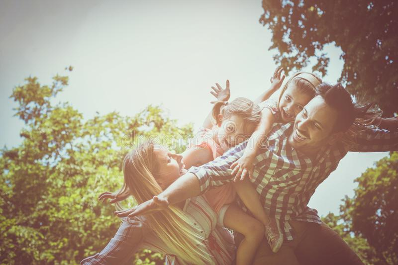 Happy family enjoying together in summer day. father carrying li stock photo