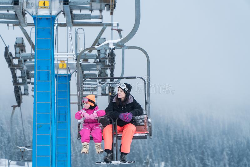 Happy family enjoying winter vacations in mountains . Mother with her daughter on the ski lift. stock image