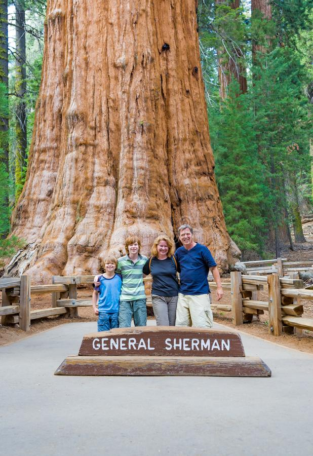 Happy family enjoys posing in sequoia national park in fromt of general sherman sequoia tree royalty free stock photography