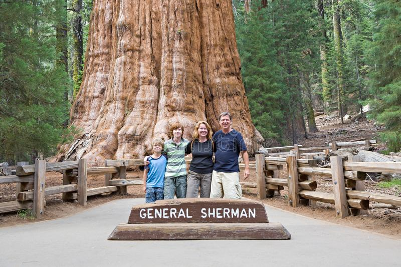 Happy family enjoys posing in sequoia national park in fromt of general sherman sequoia tree royalty free stock photos