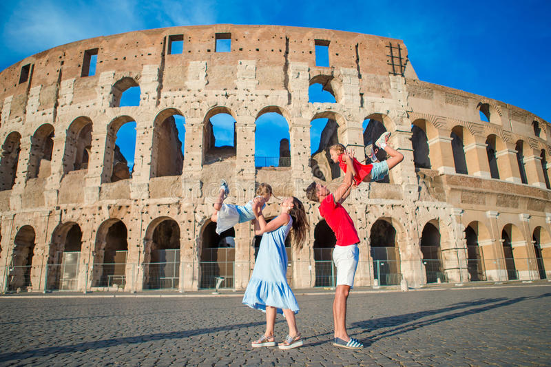 Happy family in Europe. Parents and kids in Rome over Coliseum background. royalty free stock images
