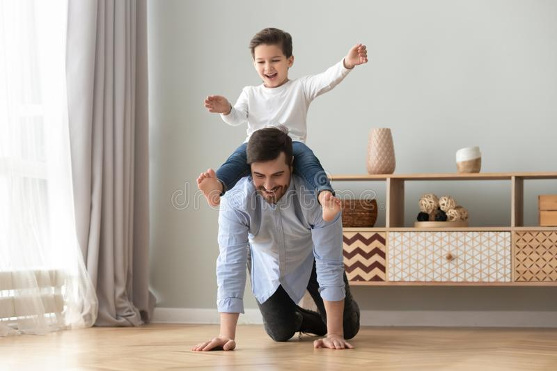 Happy family excited little boy playing with father at home. Happy funny family excited little boy playing with father at home, young dad crawling on floor royalty free stock image