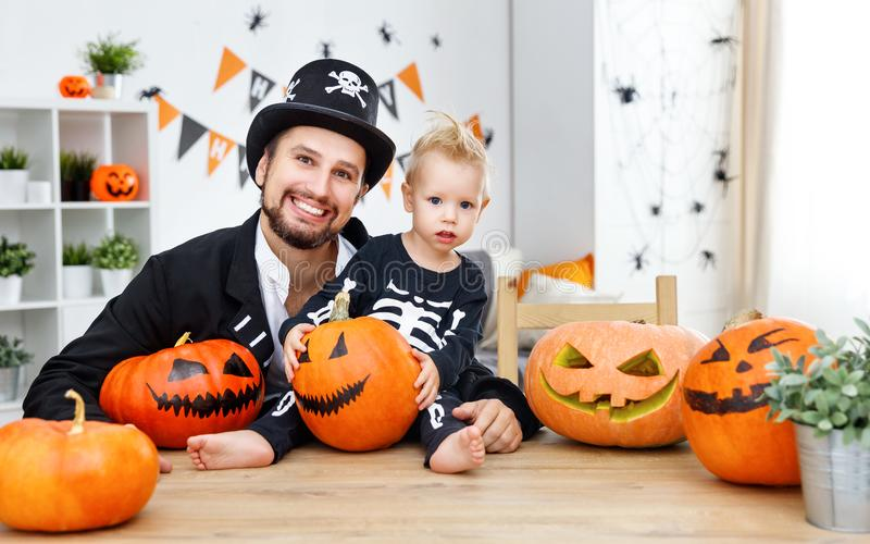 Happy family father and baby son in costumes for halloween at. A happy family father and baby son in costumes for halloween at home royalty free stock image
