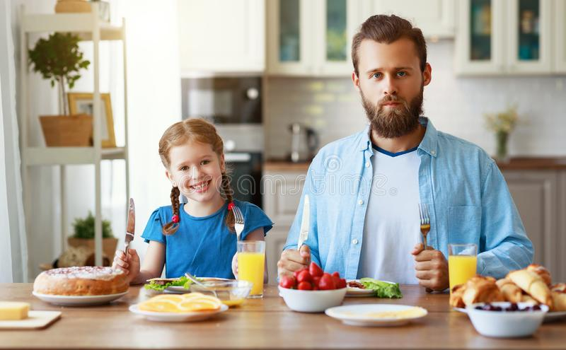Happy family father with child  feeds his   daughter in kitchen with Breakfast. Happy family father with  child  feeds his  daughter in kitchen with Breakfast stock image