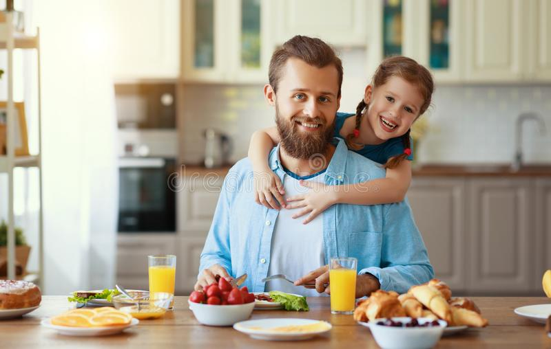 Happy family father with child  feeds his   daughter in kitchen with Breakfast. Happy family father with  child  feeds his  daughter in kitchen with Breakfast royalty free stock photography