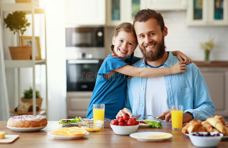 Happy family father with child  feeds his   daughter in kitchen with Breakfast. Happy family father with  child  feeds his  daughter in kitchen with Breakfast stock photo