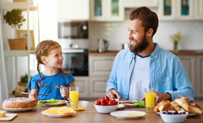 Happy family father with child  feeds his   daughter in kitchen with Breakfast. Happy family father with  child  feeds his  daughter in kitchen with Breakfast royalty free stock photos