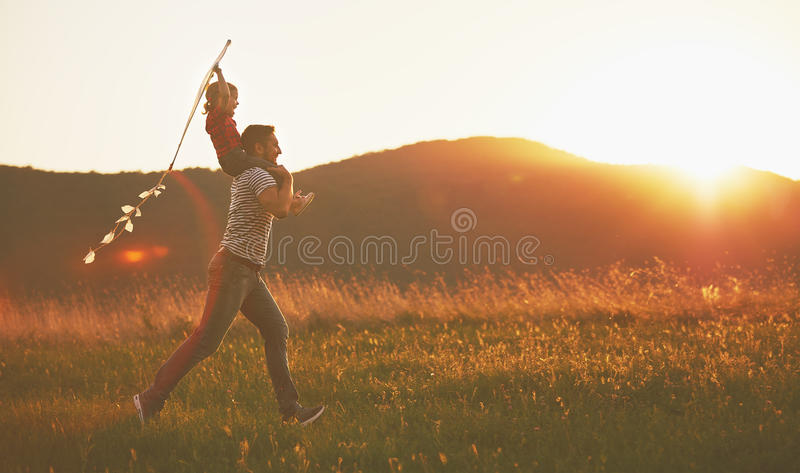 happy family father and child run on meadow with a kite in summer stock photos