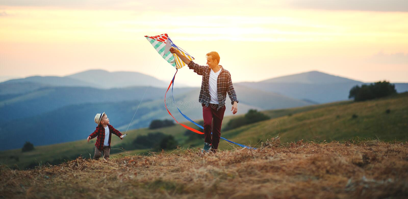 Happy family father and child son launch  kite on meadow. Happy family father and child son launch a kite on meadow royalty free stock images