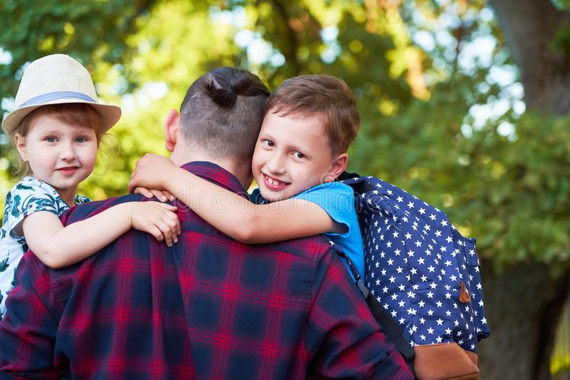 A happy family of father and children. Dad is on the hands of children in primary school. Father, son and daughter in the autumn. A happy family of father and royalty free stock photo