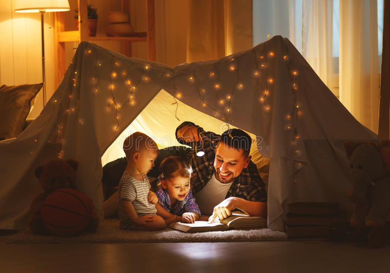 Happy Family Father And Children Reading A Book In Tent At