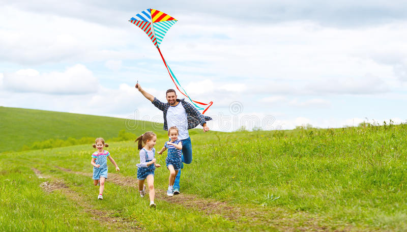 Happy family father and children run with kite on meadow stock photos