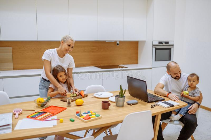 Caucasian family busy together in white kitchen stock image